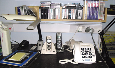 Picture of equipment to help the partially sighted including large button phones, audiobooks, and lamps